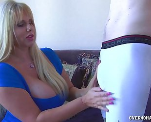 Huge-titted blond strokes a youthful guy's schlong